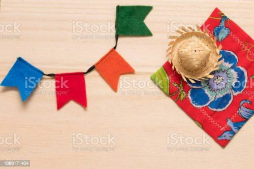 """Traditional party supplies for the typical brazilian festival """"Festa Junina"""" (June Festival) background. Cute handmade colorful flags, tiny hat and citra fabric (brazilian """"Chita"""" fabric) on wooden background. Handmande felt items"""