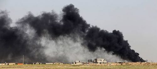 Smoke billows from what is believed to be an oil field which was set alight by Islamic State (IS) group militants in the Mkeishifa area, south of the northern Iraqi city of Tikrit, as government forces, supported by Popular Mobilization units, try to retake the area from Islamist rebels on April 9, 2015. AFP PHOTO / AHMAD AL-RUBAYE (Photo credit should read AHMAD AL-RUBAYE/AFP via Getty Images)